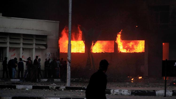 Egyptian protesters set a government building on fire during clashes with police, unseen, in Port Said, Egypt, Monday, March 4, 2013. Violence between police and protesters restarted Monday in the restive Suez Canal city of Port Said, as forces lobbed tear gas and birdshots at protesters who throw firebombs at a government complex, setting parts of it on fire. (AP Photo/Ahmed Ramadan)