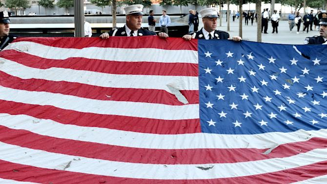 Police officers of the Port Authority of New York and New Jersey, carry an American flag that flew over at the World Trade Center towers, during the 11th anniversary ceremonies at the site of the World Trade Center, in New York, Tuesday Sept. 11, 2012. (AP Photo/Justin Lane, Pool, EPA)