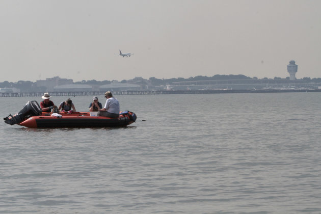 In this Wednesday, Aug. 22, 2012 photo, an airplane approaches LaGuardia Airport for landing as Ray Grizzle, left, Kerstin Kalchmayr, second from left, Allison Fitzgerald, second from right, and Loren Coen collect data at an oyster bed at Soundview Park in the Bronx borough of New York. (AP Photo/Mary Altaffer)