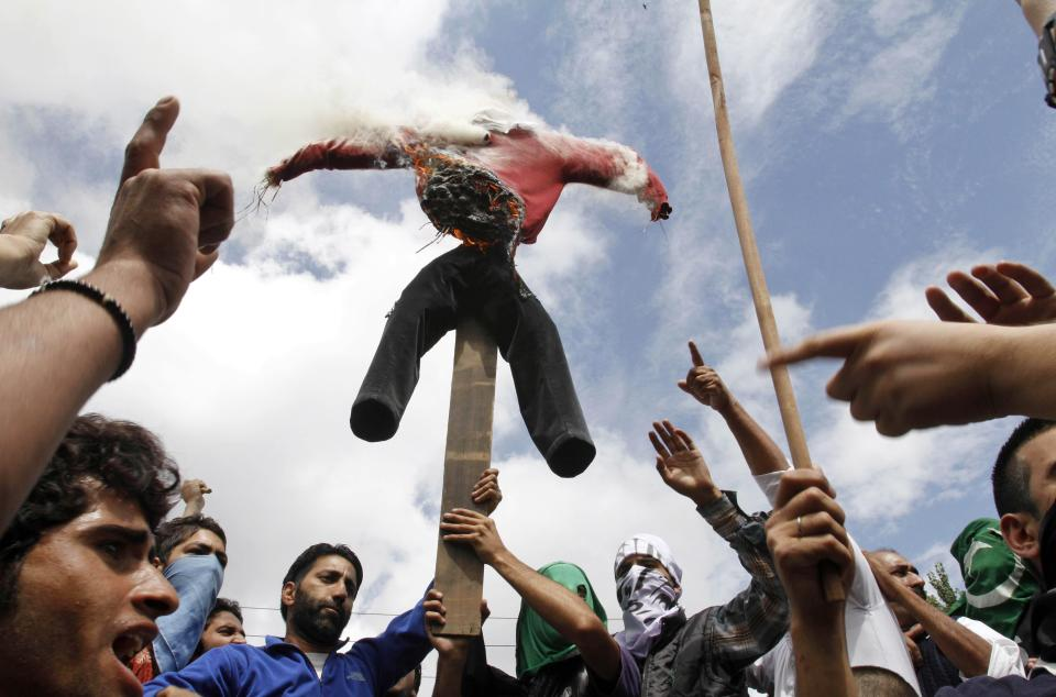 "Kashmiri Muslim protesters burn an effigy representing the United States as they shout slogans during a protest in Srinagar, India, Tuesday, Sept. 18, 2012. The protest was held against an anti-Islam film called ""Innocence of Muslims"" that ridicules Islam's Prophet Muhammad. (AP Photo/Mukhtar Khan)"