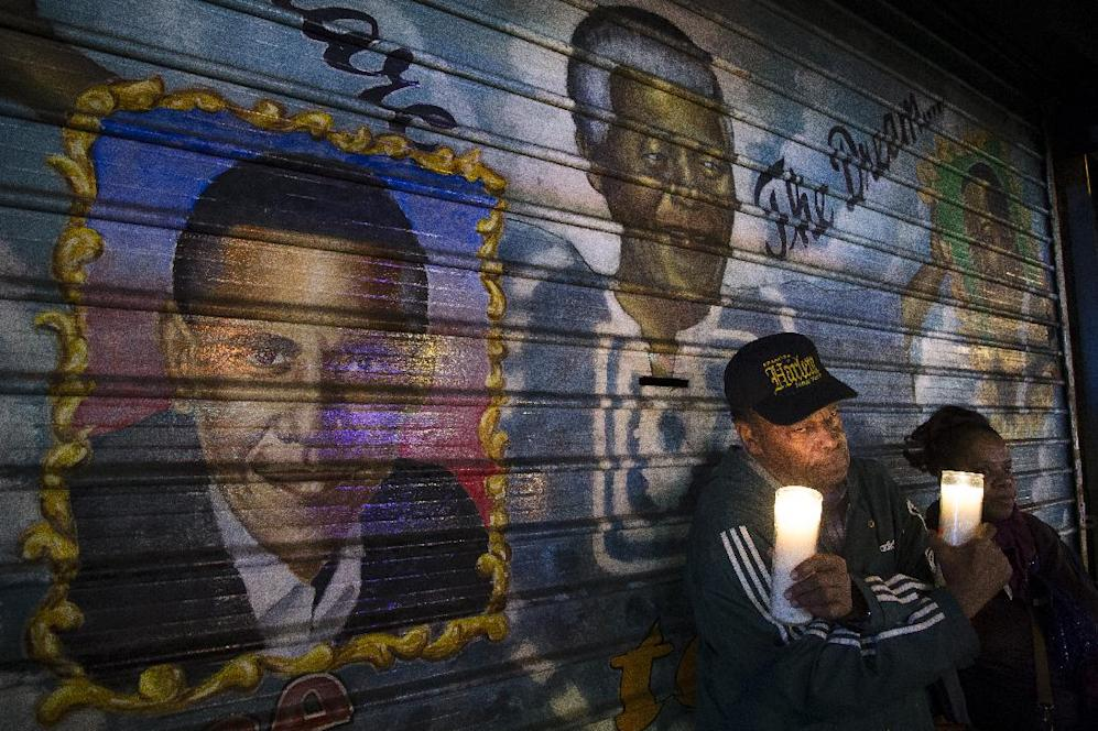 "An artist who goes by the name ""Franco the Great"" stands in front of a mural of South African leader Nelson Mandela that he painted in 1995, and later added U.S. President Barack Obama, on 125th Street in the Harlem neighborhood of New York, Thursday, Dec. 5, 2013. Mandela, South Africa's first black president, died Thursday after a long illness. He was 95. (AP Photo/John Minchillo)"