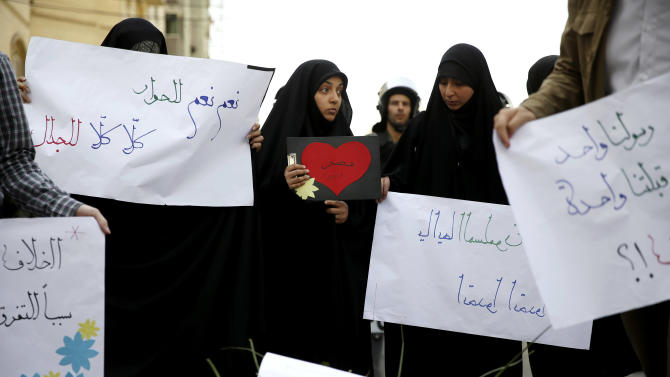 """Iranian students hold posters with Arabic that read, center left, """"yes yes to dialogue, no no to controversy,"""" and center, """"Egypt,"""" during a rally in support of solidarity with Egypt, in Tehran, Iran, Tuesday, April 9, 2013. Last week, a group of angry ultraconservative Salafis protesters threw rocks and tried to storm the residence of Iran's top diplomat in Cairo, after Iranian tourists arrived in Egypt on the first commercial flights between the two countries in 30 years. (AP Photo/Ebrahim Noroozi)"""