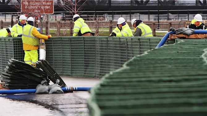 Crews with the City of Davenport build a temporary flood wall using Hesco barriers on River Drive in downtown Davenport, Iowa, Friday, April 19, 2013. (AP Photo/The Quad City Times, Kevin E. Schmidt)