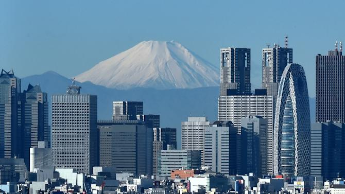 Japan's highest mountain, Mount Fuji, is seen behind the skyline of the Shinjuku area of Tokyo on December 6, 2014