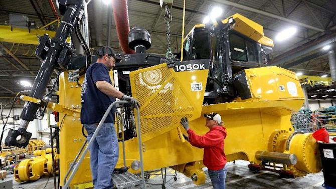FILE - In this Wednesday, Feb. 11, 2015, file photo, Rick Ring, left, and Corinne Schmitt-Bries attach a panel to a John Deere 1050K Crawler Dozer at John Deere Dubuque Works in Dubuque, Iowa. On Friday, Feb. 12, 2016, the Commerce Department releases business inventories for December. (Jessica Reilly/Telegraph Herald via AP, File) MANDATORY CREDIT