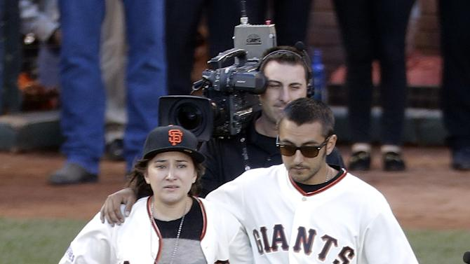 FILE - This Oct. 26, 2014, file photo shows Robin William's children Zelda, left, and Cody, walking out to the pitcher's mound before Game 5 of baseball's World Series in San Francisco. Attorneys for Robin Williams' wife and children were due back in court Friday, Aug. 28, 2015, in the ongoing fight over the late actor's estate. As court documents indicate they remain at odds over the division of Williams' personal items and a reserve fund to maintain Susan Williams in the home she shared with Robin Williams. (AP Photo/Charlie Riedel, File)