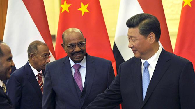 Sudanese President Omar Hassan al-Bashir looks on next to Chinese President Xi Jinxing before their meeting at the Great Hall of the People in Beijing
