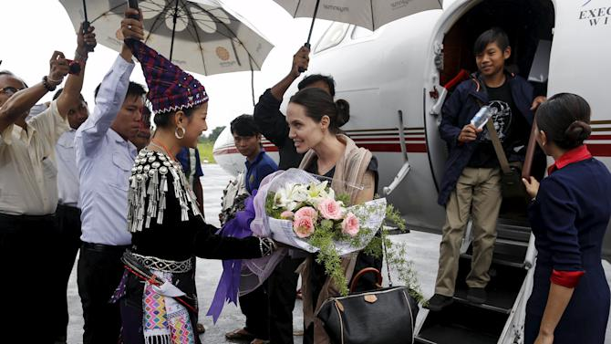 UNHCR special envoy Jolie Pitt receives flowers from a Kachin lady as she arrives at Myitkyina airport in Myitkyina capital city of Kachin state