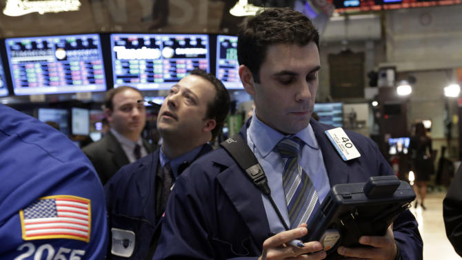 In this Monday, Feb. 25, 2013 photo, Trader Craig Spector, right, works on the floor of the New York Stock Exchange. World stock markets rose Tuesday March 5, 2013 as investors registered approval for China's spending priorities announced at its annual congress. (AP Photo/Richard Drew)
