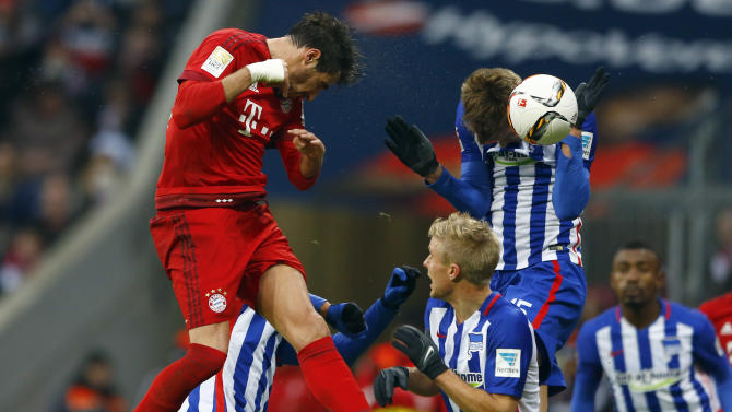 Berlin's Sebastian Langkamp, right, and Bayern's Javi Martinez challenge for the ball during the German Bundesliga soccer match between FC Bayern Munich and Hertha BSC Berlin at the Allianz Arena stadium in Munich, Germany, Saturday, Nov. 28, 2015. (AP Photo/Matthias Schrader)