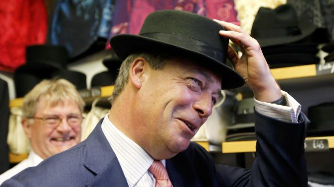 The leader of the United Kingdom Independence Party (UKIP) Nigel Farage tries on a hat during a visit to a small business that has expressed its support for the party, in Canterbury southern England
