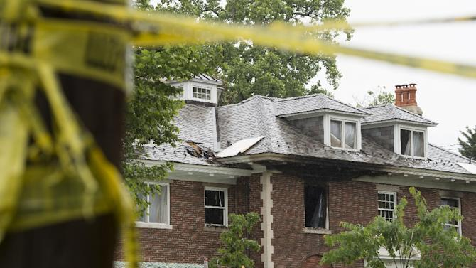 Police vehicles are seen outside a fire-damaged home where four people were killed last week in Washington, DC, May 21, 2015