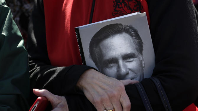 A supporter holds a book showing an image of Republican presidential candidate, former Massachusetts Gov. Mitt Romney, Monday, April 30, 2012, at a campaign rally at the Portsmouth Fish Pier in Portsmouth, N.H. (AP Photo/Jae C. Hong)