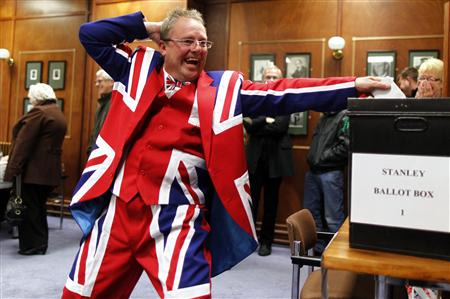 A Falkland Islander gestures as he casts his vote at the Town Hall polling station in Stanley