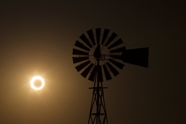 The moon passes between the sun and the earth behind a windmill near Albuquerque, New Mexico