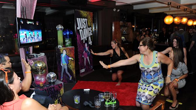 COMMERCIAL IMAGE - Guests enjoy Just Dance 4 on Kinect for Xbox 360 at Ubisoft's NYC Dance Party showcasing their upcoming line-up of dance video games, Tuesday, Aug. 21, 2012, at New York's Empire Hotel. (Photo by Diane Bondareff/Invision for Ubisoft/AP Images)