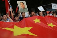 Demonstrators carry a Chinese flag during an anti-Japanese protest over the Diaoyu islands issue -- known as the Senkaku islands in Japanese -- outside the Japanese embassy in Beijing on September 15. China has postponed a ceremony marking the 40th anniversary of the establishment of diplomatic ties with Japan, due to an ongoing territorial dispute, Xinhua news agency said