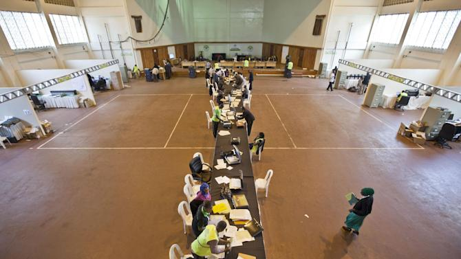 Electoral workers engage in the vote tally verification process at the National Tallying Center in Nairobi, Kenya Wednesday, March 6, 2013. Election officials in Kenya are counting by hand the ballots from the nation's presidential election after abandoning the electronic tabulation system which has posted early returns. (AP Photo/Ben Curtis)