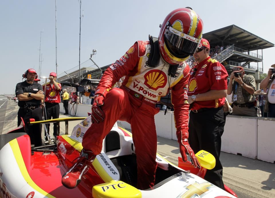 IndyCar driver Helio Castroneves, of Brazil, climbs out of his car after he qualified on the first day of qualifications for the Indianapolis 500 auto race at the Indianapolis Motor Speedway in Indianapolis, Saturday, May 19, 2012. (AP Photo/Darron Cummings)