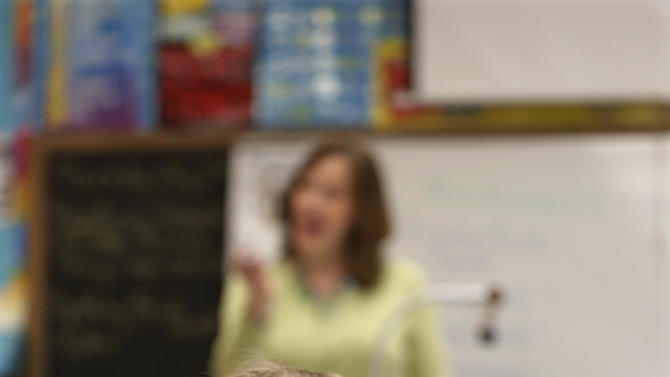 """Ryan, a """"gender variant"""" fourth grader, listens to her teacher at her school in Illinois on May 2, 2013. For Ryan, the transition began with clothing. Slowly, her cropped hair also grew long. (AP Photo/M. Spencer Green)"""