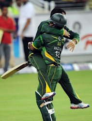Pakistani cricketer Abdul Razzaq (R) and Kamran Akmal celebrate after winning the second Twenty20 international cricket match against Australia at the Dubai international cricket stadium. Pakistan beat Australia in a tense Super over finish to the second Twenty20 international taking an unassailable 2-0 lead in the three-match series