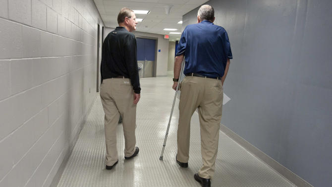 Retired Connecticut men's basketball coach Jim Calhoun, right, walks away with associate head coach George Blaney in Storrs, Conn., Thursday, Sept. 13, 2012. The 70-year-old Hall of Famer ran the men's program for 26 years and won three national titles. Assistant coach Kevin Ollie, who played for Calhoun, will be the Huskies' new coach. (AP Photo/Jessica Hill)