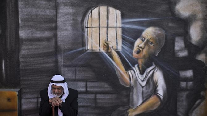 """In this Monday, June 16, 2014 photo, Palestinian refugee Shaher Alkhateeb, 73, who witnessed what the Palestinians call the """"Nakba,"""" or """"catastrophe"""" referring to their uprooting in the war over Israel's 1948 creation, poses for a picture in front of a wall painted with a mural depicting a prisoner jailed in Israel, in Kalandia refugee camp, between Jerusalem and the West Bank city of Ramallah. Alkhateeb was 6 years old when he and other 7 members of his family were forced to leave their village of Al-Burj, near the central Israeli town of Ramla and took shelter with his family in the Kalandia refugee camp. (AP Photo/Muhammed Muheisen)"""