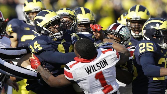 Ohio State's Dontre Wilson (1) is held back by Michigan defensive back Delano Hill (44) as the two teams scuffle during the second quarter of an NCAA college football game in Ann Arbor, Mich., Saturday, Nov. 30, 2013.  The third-ranked Buckeyes lost starting right guard Marcus Hall and kick returner Dontre Wilson and the Wolverines lost backup linebacker Royce Jenkins-Stone to ejections. All three players were flagged for unsportsmanlike conduct and had to leave the field after a skirmish