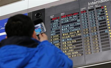 A man takes pictures of a flight information board displaying the Scheduled Time of Arrival (STA) of Malaysia Airlines flight MH370 at the Beijing Capital International Airport in Beijing, March 8, 2014. REUTERS/Kim Kyung-Hoon
