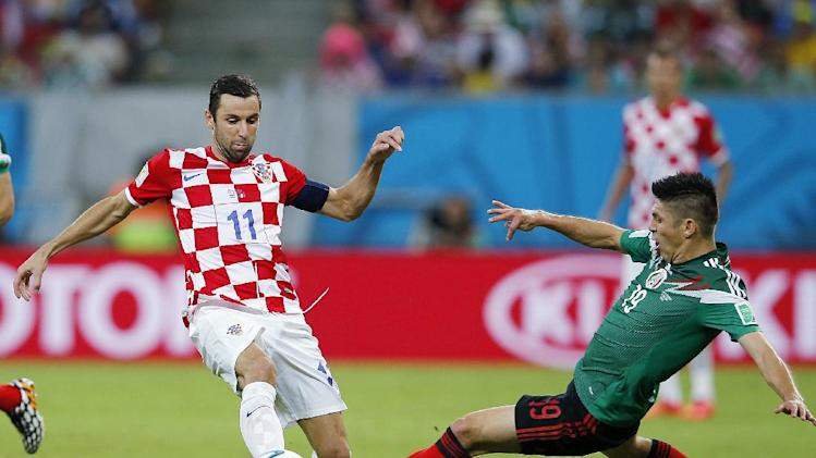 Mexico's Oribe Peralta, right, fights for the ball with Croatia's Darijo Srna  during the group A World Cup soccer match between Croatia and Mexico at the Arena Pernambuco in Recife, Brazil, Monday, June 23, 2014