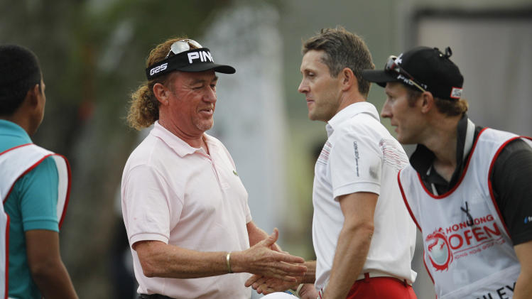 Miguel Angel Jimenez of Spain, left, shakes hands with Stuart Manley of Wales, right, after winning the Hong Kong Open golf tournament in Hong Kong, Sunday, Dec. 8, 2013. (AP Photo/Kin Cheung)