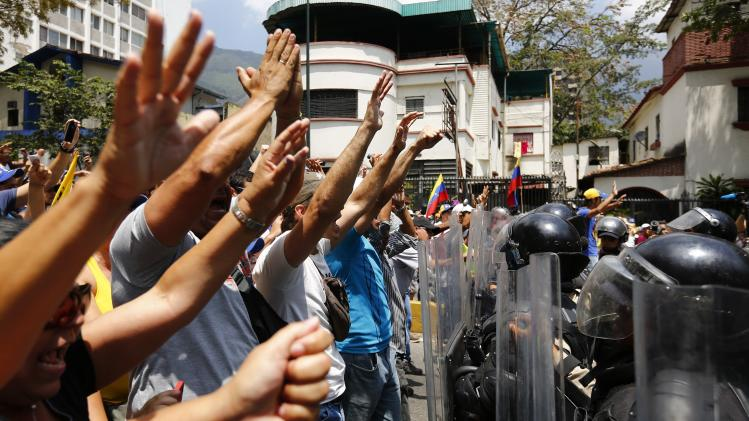 Anti-government protester raise their hands after the police attempt to stop their march in Caracas