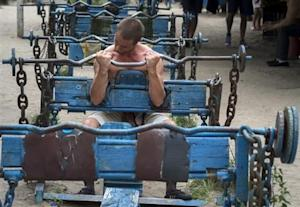 A man lifts weights as he trains at the Kachalka outdoor gym on the banks of river Dniper in Kiev