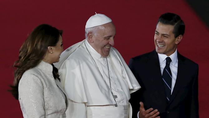 Pope Francis shares a laugh with Mexico's first lady Angelica Rivera and Mexico's President Enrique Pena Nieto after his arrival in Mexico City