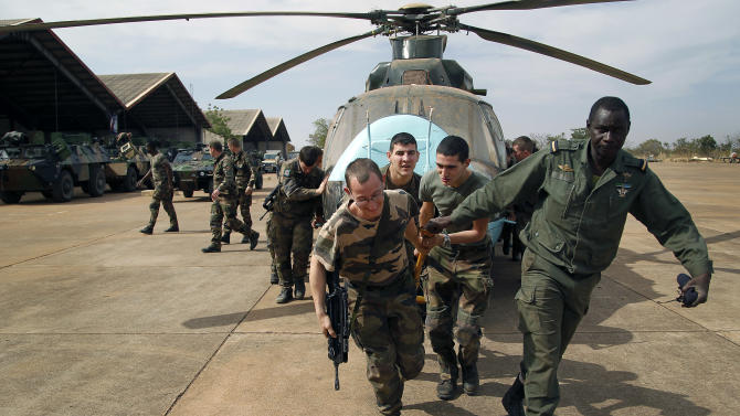 Malian soldiers helped by French troops, move a broken helicopter out a hangar to make room for more incoming troops  at Bamako's airport Tuesday Jan. 15. 2013.  French forces led an all-night aerial bombing campaign Tuesday to wrest control of a small Malian town from armed Islamist extremists who seized the area, including its strategic military camp. A a convoy of 40 to 50 trucks carrying French troops crossed into Mali from Ivory Coast as France prepares for a possible land assault. Several thousand soldiers from the nations neighboring Mali are also expected to begin arriving in coming days. (AP Photo/Jerome Delay)