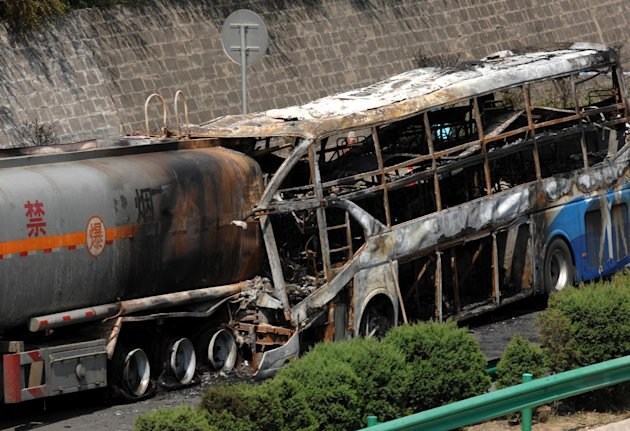In this photo released by China&#39;s Xinhua News Agency, the burnt wreckage of a double-decker sleeper bus and a tanker loaded with highly-flammable methanol sit on a highway in Yan&#39;an City, northwest China&#39;s Shaanxi province on Sunday, Aug. 26, 2012. The 39-seat bus rammed into the tanker early Sunday, causing both vehicles to burst into flames and killing 36 people, state media said. (AP Photo/Xinhua, Li Yibo) NO SALES