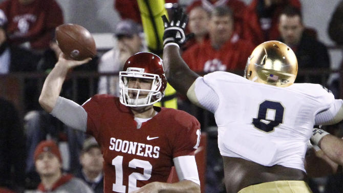 Oklahoma quarterback Landry Jones (12) passes in front of Notre Dame linebacker Kendall Moore (8) during the third quarter of an NCAA college football game in Norman, Okla., Saturday, Oct. 27, 2012. Notre Dame won 30-13. (AP Photo/Alonzo Adams)