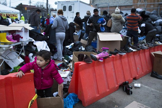 A young girl plays as residents search through donated clothing piles in the Rockaways, Saturday, Nov. 10, 2012, in the Queens borough of New York. Despite power returning to many neighborhoods in the