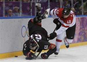Canada's Nash is flipped in the air by Austria's Iberer during the third period of their men's preliminary round hockey game at the 2014 Sochi Winter Olympic Games
