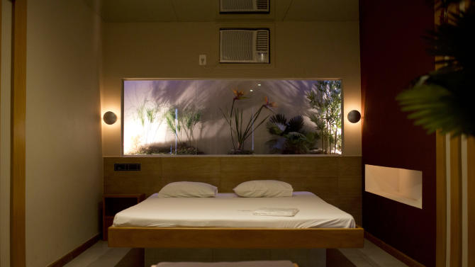 """A newly remodeled room is seen at the Shalimar Hotel, known as a love hotel in Rio de Janeiro, Brazil, Thursday, Jan. 17, 2013. Like about a third of city's 180 hotels that rent rooms by the hour, mostly for amorous rendezvous, the Shalimar is trading its oversized beds and bondage-ready chairs for proper couches, functional desks and other business-friendly furnishings. The goal is reinvention as a standard pay-by-the-day tourist hotel, after the government slashed property taxes for love hotels, known as """"motels"""" in Portuguese, that agree to tone down the decor and free up 90 percent of their rooms for the tsunami of visitors expected to flood the city for the 2014 World Cup soccer tournament and the 2016 Olympic Games. (AP Photo/Felipe Dana)"""