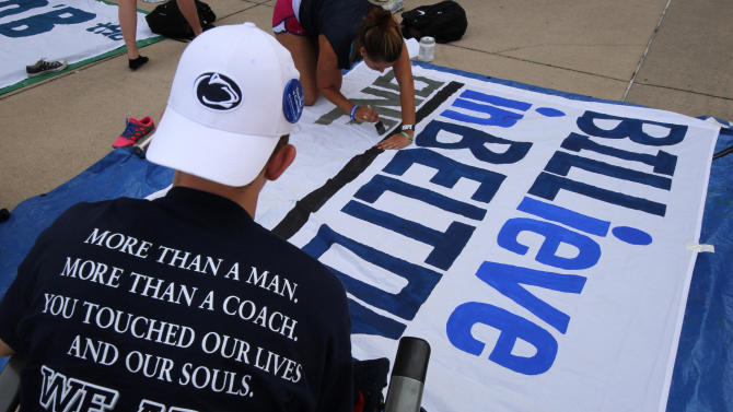 Residents of Nittanyville, the student tent village outside gate A of Beaver Stadium, Dan Arnoldi, left, a Penn State senior from Wanaque, N.J., watches as Karisa Maxwell, top, a senior from Otisville, N.Y., paints a sign supporting new Penn State head football coach Bill O'Brien, and running back Bill Belton in State College, Pa., Friday, Aug. 31, 2012. Penn State football opens it's season at home Saturday against Ohio University. (AP Photo/Gene J. Puskar)
