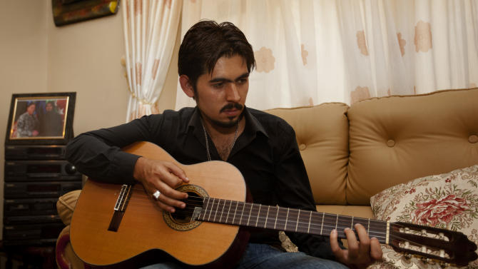 In this photo taken on Aug. 8, 2011. Ahmad Taki, a human resources manager at the main international military base, plays guitar at his residence in Kabul, Afghanistan. Ahmad Taki has braved threatening phone calls and risked being targeted by the Taliban in the hope that his job with the Americans would provide a ticket to the United States. Now, nearly nine months after applying for a visa program for cases like his, he's heard nothing and feels abandoned by the people for whom he's risked his life.  (AP Photo/Dar Yasin)