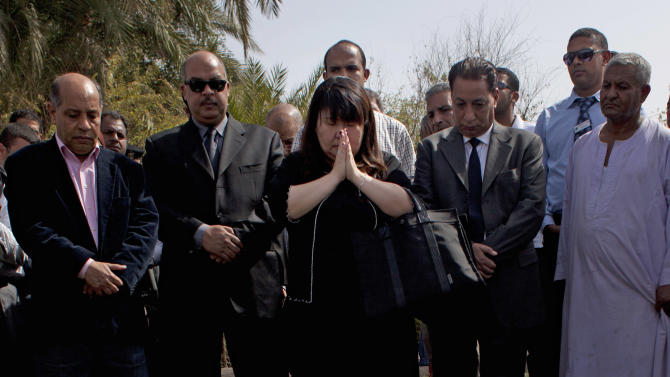 Japanese travel agent Okumura Hatsuko, center, pays respect to Japanese tourists that died from a hot air balloon accident, in Luxor, Egypt, Wednesday, Feb. 27, 2013. A hot air balloon carrying tourists over Egypt's ancient city of Luxor caught fire on Tuesday, Feb. 26, 2013 and some passengers trying to escape the flames leaped to their deaths before the craft crashed in a sugar cane field. At least 19 tourists were killed in one of the world's deadliest ballooning accidents. (AP Photo/Nasser Nasser)