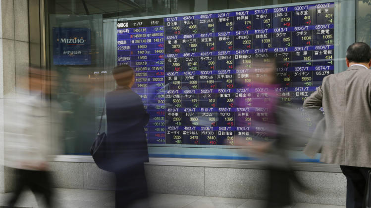 A man looks at the electronic stock board of a securities firm in Tokyo, Wednesday, Nov. 13, 2013. Asian stock markets sank Wednesday after a highly anticipated meeting of Chinese leaders did not announce bold reforms to overhaul a growth model that is running out of steam. (AP Photo/Shizuo Kambayashi)
