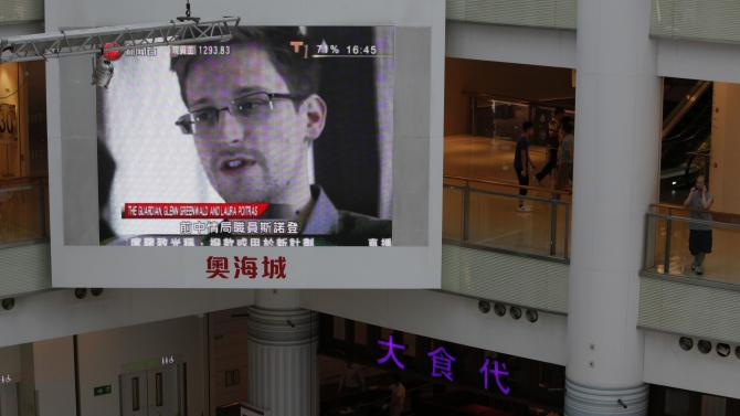 A TV screen shows the news of Edward Snowden, a former CIA employee who leaked top-secret documents about sweeping U.S. surveillance programs, at a shopping mall in Hong Kong Friday, June 21, 2013. President Barack Obama is holding his first meeting with a privacy and civil liberties board Friday as he seeks to make good on his pledge to have a public discussion about secretive government surveillance programs. (AP Photo/Kin Cheung)