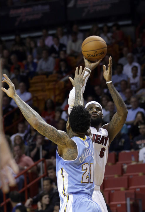 Miami Heat forward LeBron James (6) prepares to shoot as Denver Nuggets forward Wilson Chandler (21) defends during the first half of an NBA basketball game in Miami, Friday, March 14, 2014. (AP Photo