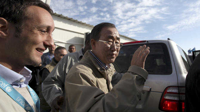"""The United Nations Secretary-General Ban Ki-moon waves to U.N. aid workers during a visit to Zaatari Syrian refugee camp, in Mafraq, Jordan, near the Syrian border, Saturday, Dec. 7, 2012. U.N. Secretary-General Ban Ki-Moon on Friday called on the Syrian government to """"stop the violence in the name of humanity"""", during a visit to the Zaatari refugee camp in Jordan, close to the Syrian border. (AP Photo/Mohammad Hannon)"""