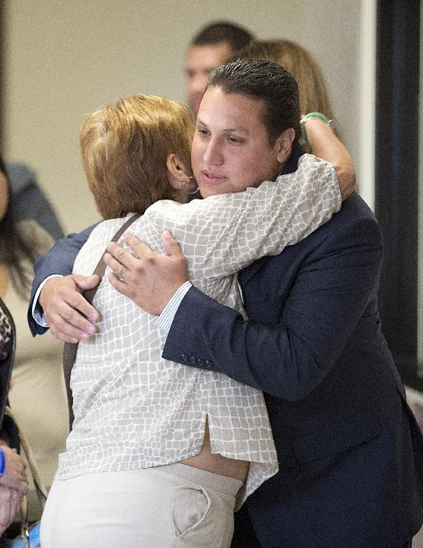 In this Tuesday, Aug. 19, 2014, photo, a relative hugs David Barajas before he enters the court in Angleton, Texas. David Barajas is accused of fatally shooting Jose Banda in December 2012 near Alvin minutes after Banda plowed into a vehicle that Barajas and his two sons had been pushing on a rural road. Twelve-year-old David Jr. and 11-year-old Caleb were killed. Barajas' truck had run out of gas about 100 yards from the family's home (AP Photo/Houston Chronicle, Thomas B. Shea)