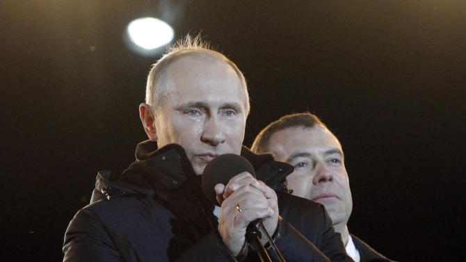 Russian Prime Minister and presidential candidate Vladimir Putin, left, flanked by President Dmitry Medvedev, has tears in his eyes as he addresses a massive rally of his support at Manezh square outside Kremlin, in Moscow, Russia, Sunday, March 4, 2012. Vladimir Putin has claimed victory in Russia's presidential election, which the opposition and independent observers say has been marred by widespread violations. Putin made the claim at a rally of tens of thousands of his supporters just outside the Kremlin, thanking his supporters for helping foil foreign plots aimed to weaken the country.   (AP Photo/Ivan Sekretarev)