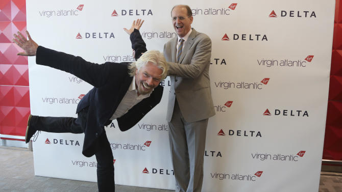 Virgin CEO Richard Branson, left, and Delta airlines CEO Richard Anderson pose for photographers inside the new Delta terminal 4 at JFK airport, Friday, May 24, 2013 in New York. Delta opened its new $1.4 billion terminal, strengthening its hand in the battle for the lucrative New York travel market. The expanded concourse offers sweeping views of the airport, upscale food and shopping options and increased seating. It replaces a decrepit terminal built by Pan Am in 1960 that was an embarrassing way to welcome millions of visitors to the United States. (AP Photo/Mary Altaffer)